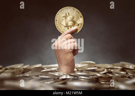People hand showing golden bitcoin between coin pile with black background - Stock Photo
