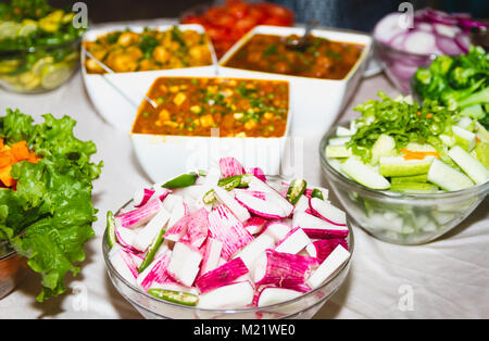 Fresh salads and pickles on bowls at the party - Stock Photo