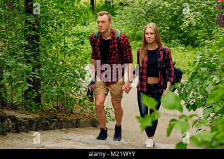 Skateboarders couple to go upstairs in nature parks. - Stock Photo
