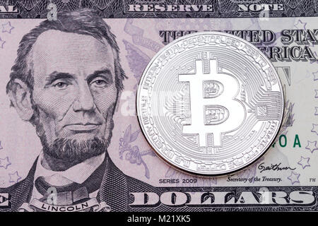 Photo of silver bitcoin on dollar banknote background. - Stock Photo