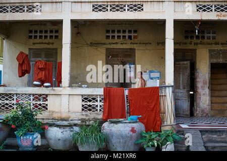 Buddhist Monk in front of monastry rooms, Battambang, Cambodia - Stock Photo