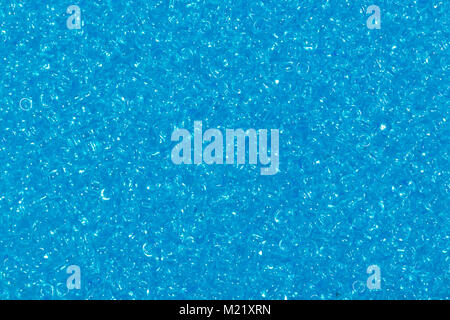 Photograph of multicolored blue glass seed beads background.