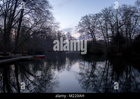 River in Tiergarten, showing water, trees and a boat. - Stock Photo