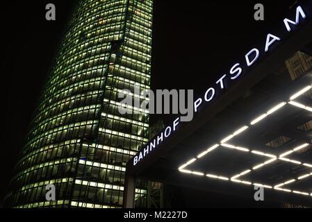 Modern office building on Potsdam square in Berlin illuminated at night. Entrance to Potsdamer Platz Railway Station - Stock Photo