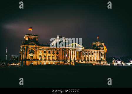 Illuminated Reichstag building at night in Berlin, Germany - Stock Photo