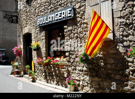 The Catalonian flag hangs outside a bakery on a pretty street in the pretty walled town of Villfranche de Conflent - Stock Photo