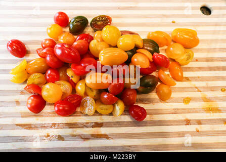 A pile of juicy multi-colored grape tomatoes chopped in half on a stiped wood cutting board ready to add to dish - Stock Photo