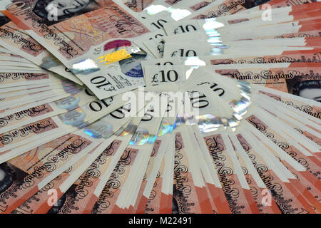 A lot of money in cash and ten pound notes on a table fanned out in a carousel design. Ten pound notes in readies - Stock Photo