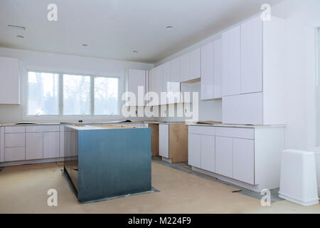 Custom kitchen cabinets in various stages of installation base for island in center Installation of kitchen cabinets - Stock Photo