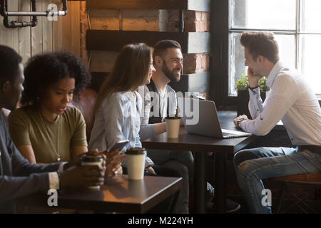Diverse multiracial young people talking drinking coffee in cozy - Stock Photo
