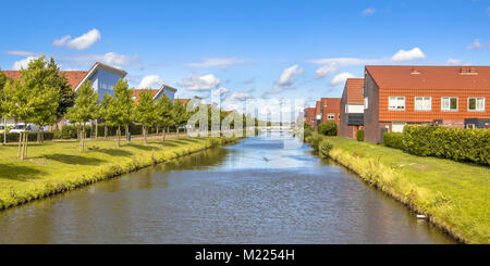 River in modern suburb neigborhood with houses along ecological park - Stock Photo