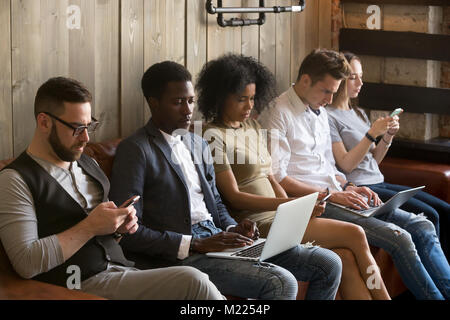 Multiracial black and white people sitting on couch using device - Stock Photo