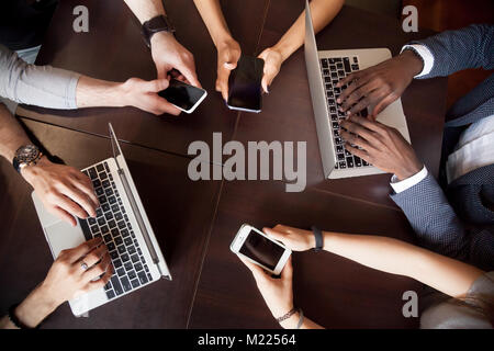 Diverse multiracial people using laptops smartphones on table, t - Stock Photo