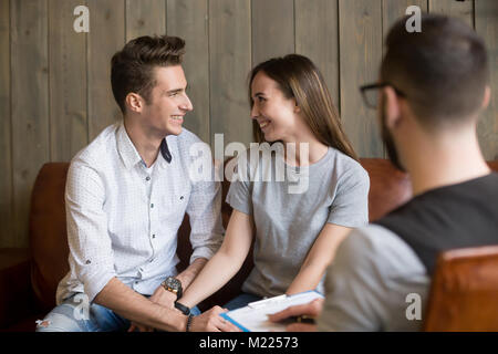 Happy young reconciled couple making up during counseling therap - Stock Photo