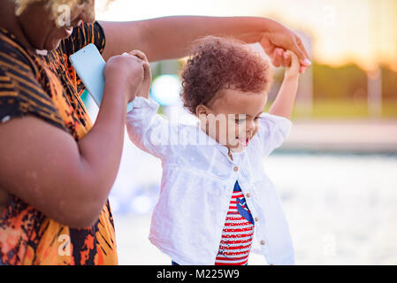 Baby daughter's first steps - Stock Photo