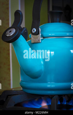 A blue metal teapot heating water on a propane gas stove. - Stock Photo