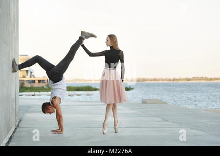 A slender ballerina dances with a modern dancer. Dating lovers. Passion and romance of dance. He stands on his hands. - Stock Photo