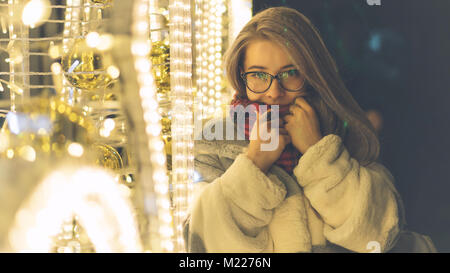 A young sweet hipster girl with glasses and a warm scarf walks by the mall on a holiday. She smiles and straightens - Stock Photo