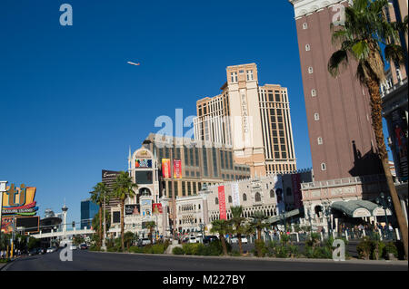 Passenger airplane taking off over Las Vegas. Palazzo and Venetian hotels on the right side. - Stock Photo