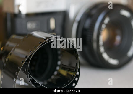 Single-lens reflex camera with roll of Kodak safety film in foreground. - Stock Photo
