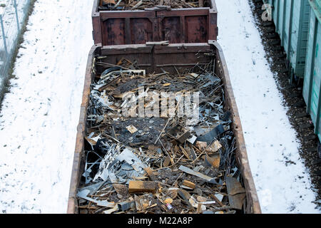 Railway wagon in winter filled with metal scrap. Old rusty corroded metal, abstract for ecology - Stock Photo