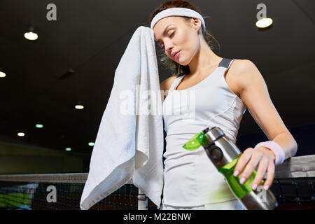 Waist up portrait of female tennis player wiping forehead with towel  taking break from practice in indoor court, - Stock Photo