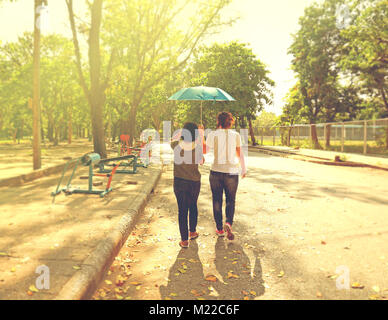 Best female friends sharing an umbrella while walking together in a park with strong sunshine during day time - Stock Photo