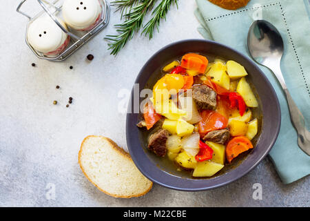 Beef stew  with vegetables in tomato sauce (carrots, tomatoes, saucesweet pepper, potatoes, paprika) on a stone - Stock Photo