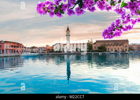 sunset over in Zaante town harbor, Zakinthos Greece with flowers - Stock Photo