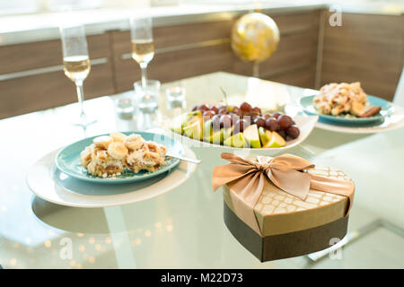 Background image of dinner table for two served  for romantic date on Valentines day ,  focus on heart shaped box - Stock Photo