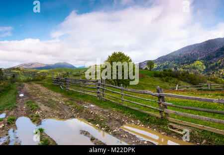 country road through mountainous rural area. beautiful springtime scenery with agricultural fields and grassy slopes - Stock Photo