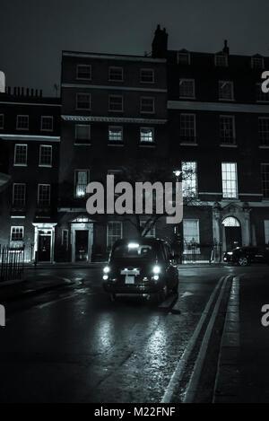 London cab passing by posh Georgian houses at night in Mayfair, London, England, UK - Stock Photo