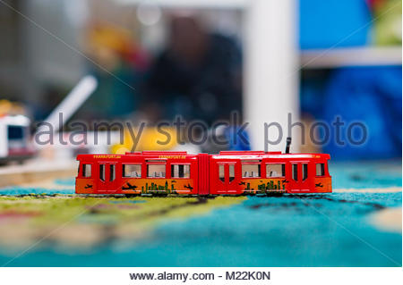 Red Siku brand toy tram on a floor of a play room in soft focus - Stock Photo