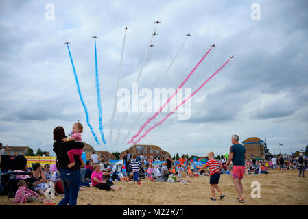RAF Red Arrows at the Clacton Airshow arriving over the beach with people watching - Stock Photo