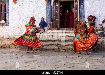 Prakhar Lhakhang, Bumthang, Bhutan.  Young Buddhist Monks in Monastery Doorway Watching  Senior Monks Wearing Masks - Stock Photo