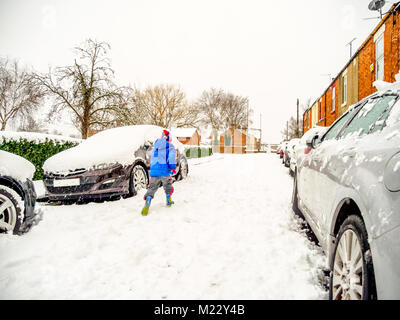 Cloudy winter day view of young boy running on typical snowy british road between parked cars in blue jacket and - Stock Photo