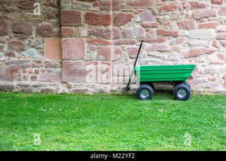 A green garden pushcart, wheelbarrow on the green grass field with old brick wall in the background. - Stock Photo