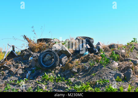 Old tires thrown in a pile on a small mound of dirt with weeds growing around them.  Rocks are in the surrounding - Stock Photo