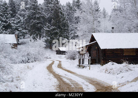 Snow covered wooden cabins at the Garnet Ghost Town, on Bear Gulch, northwest of Drummond, Montana.  The mines in - Stock Photo