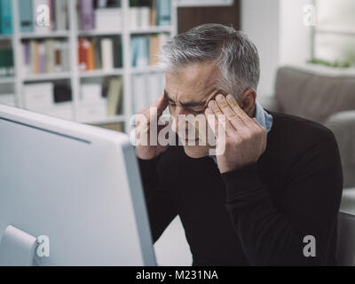 Tired overworked businessman having a bad headache, he is massaging his temples: stress and deadlines concept - Stock Photo
