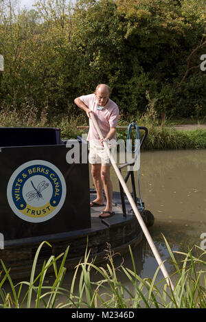 Man standing on the stern of a canalboat casting off from the shore using a long wooden pole - Stock Photo