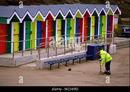 Clearing away of sand which was blown over the sea wall during a strong wind at the beach hut area at Whitmore Bay, - Stock Photo