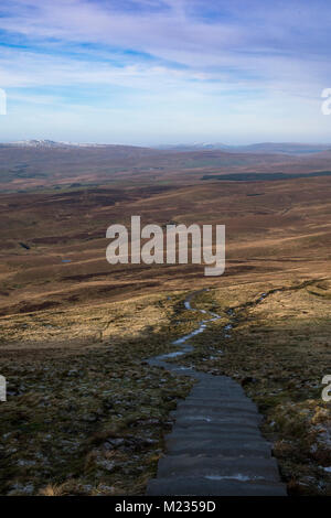 Paved steps leading down from the summit of Pen-y-ghent towards Hull Pot along the Pennine Way route. - Stock Photo