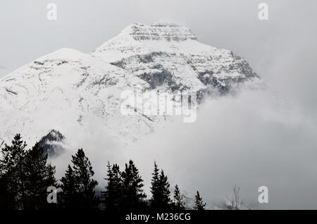 High in the snow covered mountains a foggy freezing rain cloud begins to cover the view of the mountains with the - Stock Photo