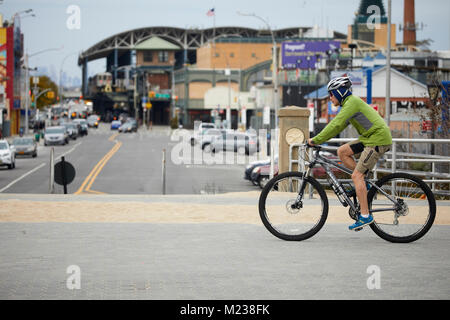 New York city  Coney Island–Stillwell Avenue Subway terminal in Brooklyn, cycling bike cyclist  on the beach promenade - Stock Photo