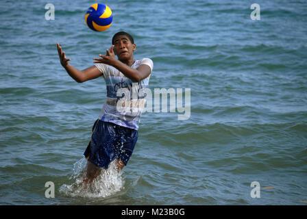 Fijian Boy playing with soccer ball in the sea, Palm Beach, Fiji. - Stock Photo