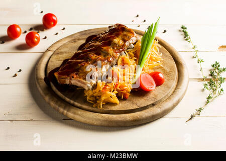 Roast ribs drizzled with sauce with stewed cabbage on a round wooden Board - Stock Photo