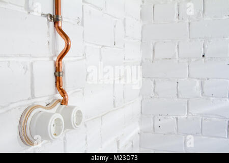 Retro socket made of white ceramic with open electrical wiring. Against the background of a white brick wall, electrical - Stock Photo