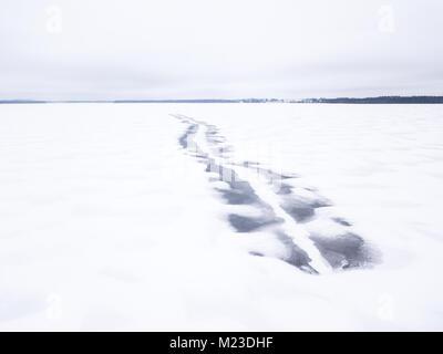 Melted dark snowmobile tracks on a frozen snow covered lake. Tartu, Estonia. - Stock Photo