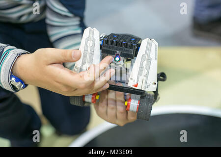 robotics, entertainment, childhood concept. in the arms of small boy there is robot made of lego parts, wheels and - Stock Photo